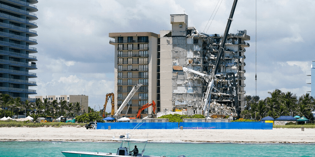 A Miami-Dade County Police boat patrols in front of the Champlain Towers South condo building, where search and rescue efforts continue more than a week after the building partially collapsed, Friday, July 2, 2021, in Surfside, Fla.