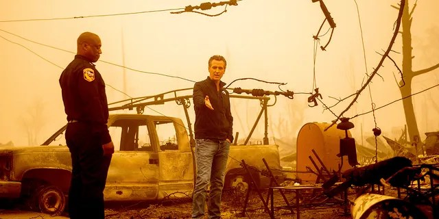 California Gov. Gavin Newsom examines a scorched utility pole while surveying Dixie Fire damage in Greenville on Saturday, Aug. 7, 2021, in Plumas County, California. Accompanying him is Cal Fire Assistant Region Chief Curtis Brown. (Associated Press)