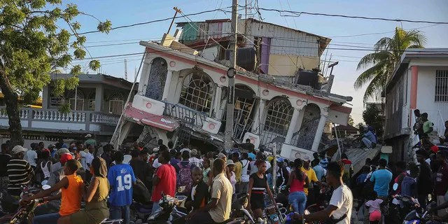 People gather outside the Petit Pas Hotel, destroyed by the earthquake in Les Cayes, Haiti, Saturday, Aug. 14, 2021. A 7.2 magnitude earthquake struck Haiti on Saturday, with the epicenter about 125 kilometers (78 miles) west of the capital of Port-au-Prince, the US Geological Survey said.