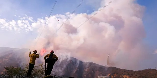 Firefighters watch as a helicopter drops water at the South Fire burning in Lytle Creek, San Bernardino County, north of Rialto, Calif., Wednesday, Aug. 25, 2021.