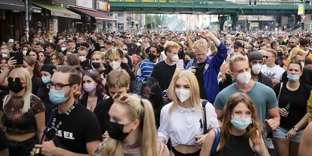 People, most of them wearing masks, dance behind a truck as they attend a demonstration named 'Train of Love' in Berlin, Germany, Saturday, Aug. 28, 2021.