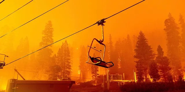 Seen in a long camera exposure, the Caldor Fire burns as a chair lift sits at the Sierra-at-Tahoe ski resort on Sunday, Aug. 29, 2021, in Eldorado National Forest, Calif. The main buildings at the ski slope's base survived as the main fire front passed.