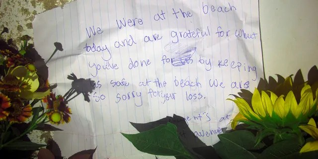 A note left with flowers is seen placed by a lifeguard chair on the sand at the beach in Berkeley Township, N.J., where a young lifeguard was killed and seven others injured by a lightning strike, Monday, Aug. 30, 2021. (AP Photo/Wayne Parry)