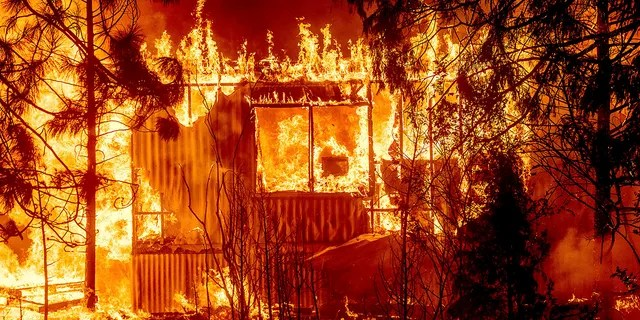Flames consume a home on Highway 89 as the Dixie Fire tears through the Greenville community of Plumas County, Calif., on Wednesday, Aug. 4, 2021. The fire leveled multiple historic buildings and dozens of homes in central Greenville. (AP Photo/Noah Berger)