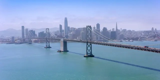 Aerial view of the San Francisco-Oakland Bay Bridge with modern cityscape in background, San Francisco, California, USA.