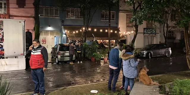 People gather outside on the sidewalk after a strong earthquake was felt, in the Roma neighborhood of Mexico City, Tuesday, Sept. 7, 2021. (AP Photo/Leslie Mazoch)
