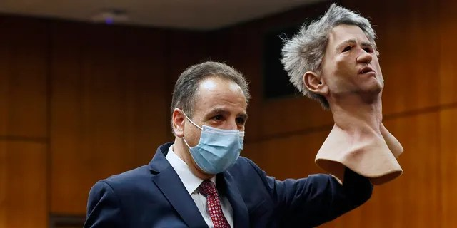 Deputy District Attorney Habib A. Balian holds a rubber latex mask, worn by Robert Durst when police arrested him.