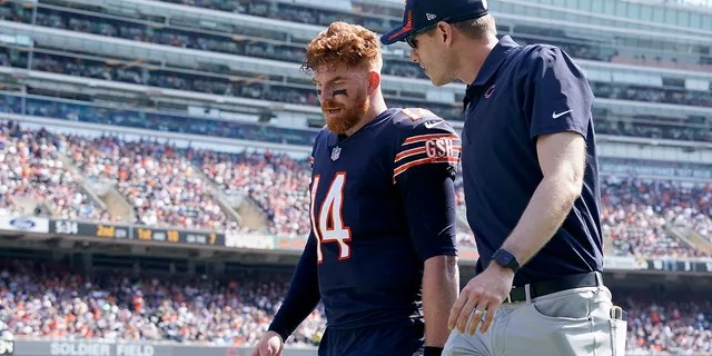 Chicago Bears quarterback Andy Dalton walks to the locker room with a trainer during the first half of an NFL football game against the Cincinnati Bengals Sunday, Sept. 19, 2021, in Chicago.