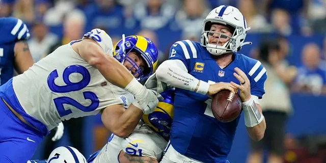 Indianapolis Colts quarterback Carson Wentz (2) is sacked by Los Angeles Ram Greg Gaines (91) during the first half of an NFL football game, Sunday, Sept. 19, 2021, in Indianapolis.