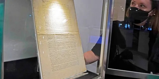 Ella Hall, a specialist in books and manuscripts at Sotheby's, New York, holds a 1787 printed copy of the US Constitution in her display case.  It is the only copy that remains in private hands and is estimated at $15 million–$20 million.  (AP Photo/Richard Drew)