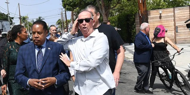 VENICE, CA. September 8, 2021:Republican gubernatorial candidate Larry Elder is escorted by a security guard as a few homeless people yell during a tour in Venice Wednesday. (Wally Skalij/Los Angeles Times via Getty Images)