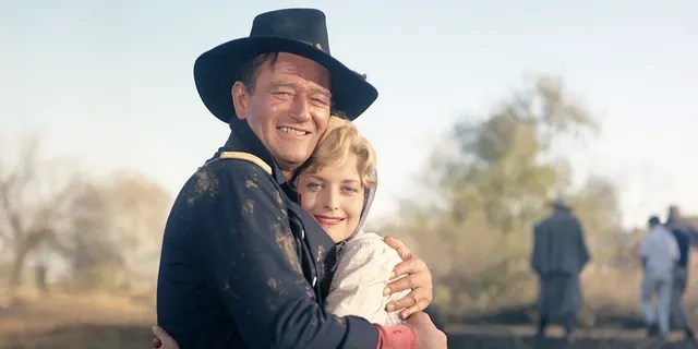 """John Wayne and Constance Towers on the set of """"The Horse Soldiers,"""" directed by John Ford."""