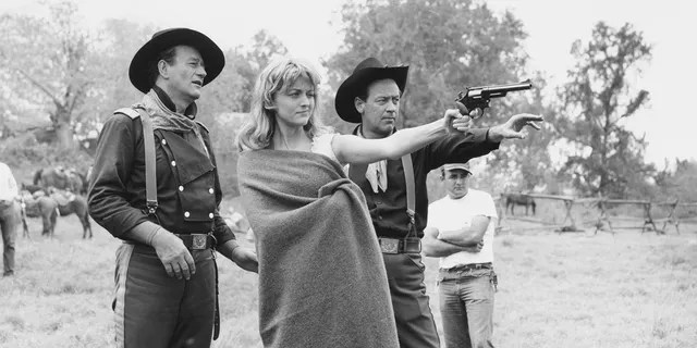 John Wayne and William Holden assist Constance Towers in aiming a revolver on the set.