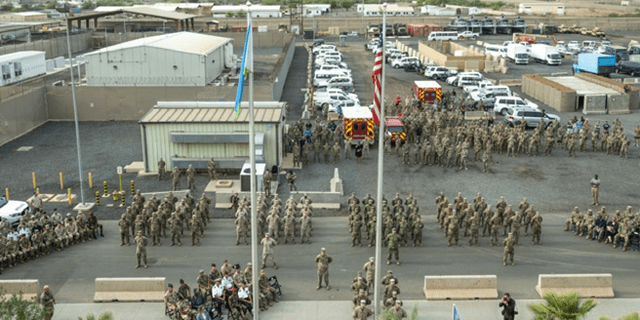 Service member with Joint Combined Task Force - Horn of Africa, stand in formation during a Patriot's Day ceremony at Camp Lemonnier, Djibouti, Sept. 11, 2021, commemorating the 20th anniversary of the terrorist attacks on Sept. 11, 2001. The memorial ceremony included a joint formation, a multi-aircraft flyover, presentation of colors and the playing of Taps. Camp Lemonnier held multiple events in honor and remembrance of those who lost their lives both on that day and over the past two decades fighting the Global War on Terror.