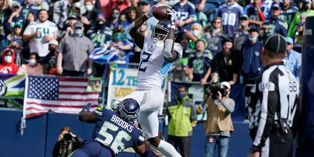 Tennessee Titans wide receiver Julio Jones (2) makes a catch in the end zone above Seattle Seahawks linebacker Jordyn Brooks (56), but came down with one foot out of bounds during the first half of an NFL football game, Sunday, Sept. 19, 2021, in Seattle.