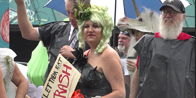 """A woman holds a """"Let them eat trash"""" sign while wearing a garbage bag for a dress at an organized 'trash parade' protest."""