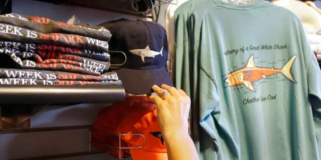In this July 2, 2014 photo, a customer examines shark-themed clothing at a store in Chatham, Massachusetts.