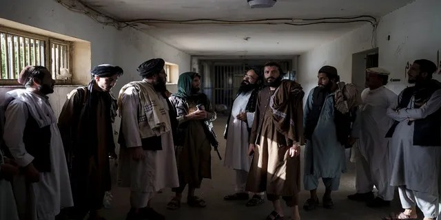 Taliban fighters, some former prisoners, chat in an empty area of the Pul-e-Charkhi prison in Kabul, Afghanistan, on Monday.
