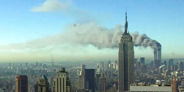 FILE - The twin towers of the World Trade Center burn behind the Empire State Building, Tuesday Sept. 11, 2001. in New York.