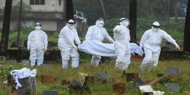 Sept. 5, 2021: People in protective suits prepare to cremate the body of a 12-year-old boy who died of the Nipah virus in Kozhikode, Kerala state, India.