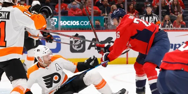 Washington Capitals center Nic Dowd (26) checks Philadelphia Flyers center Sean Couturier (14) during the third period Oct. 8, 2021, at Capital One Arena in Washington, D.C.