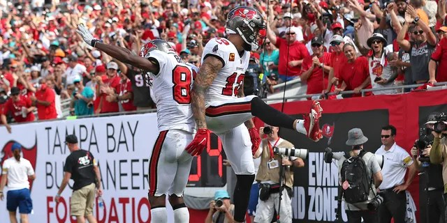 Tampa Bay Buccaneers wide receiver Mike Evans (13) celebrates his score against the Miami Dolphins with wide receiver Antonio Brown (81) during the second half of an NFL football game Sunday, Oct. 10, 2021, in Tampa, Fla.