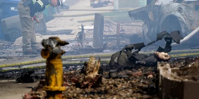 A fire official looks over the scene of a small plane crash, Monday, Oct. 11, 2021, in Santee, Calif.