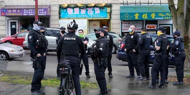 Seattle Police officers confer after taking part in a public roll call at Hing Hay Park in Seattle's Chinatown-International District Thursday, March 18, 2021. Seattle's police department is having detectives and non-patrol staff respond to emergency calls because of a shortage of officers union leaders fear will be made worse by COVID-19 vaccine mandates.