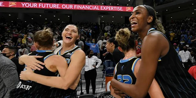 Chicago Sky's Astou Ndour-Fall, right, Courtney Vandersloot (22), Stefanie Dolson second from left, and Allie Quigley celebrate after the Sky defeated the Connecticut Sun 79-69 in Game 4 of a WNBA basketball semifinal series Wednesday, Oct. 6, 2021, in Chicago.