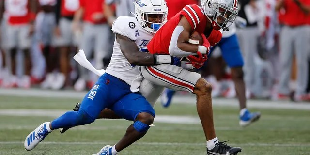 Tulsa defensive back TieNeal Martin, left, tackles Ohio State receiver Chris Olave during the second half of an NCAA college football game Saturday, Sept. 18, 2021, in Columbus, Ohio.