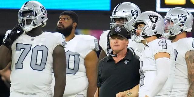 Las Vegas Raiders head coach Jon Gruden talks with quarterback Derek Carr (4) during the second half against the Los Angeles Chargers at SoFi Stadium in Inglewood, California.