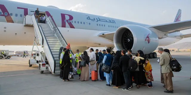 Afghan passengers are pictured in-front of a Qatar Airways airplane at Kabul International Airport, in Kabul, Afghanistan September 19, 2021. Qatar's Ministry of Foreign Affairs/Handout via REUTERS ATTENTION EDITORS - THIS IMAGE HAS BEEN SUPPLIED BY A THIRD PARTY. NO RESALES. NO ARCHIVES.