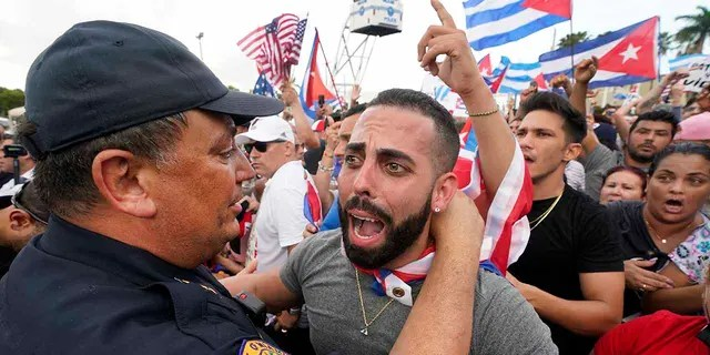 In this Wednesday, July 14, 2021, file photo, Miami Police Chief Art Acevedo, left, hugs a demonstrator, in Miami's Little Havana neighborhood.