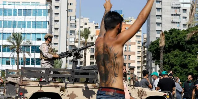 An army soldier stands on a vehicle as a supporter of the Shiite Hezbollah flashes the victory sign during armed clashes that erupted during a protest in the southern Beirut suburb of Dahiyeh, Lebanon, Thursday, Oct. 14, 2021. Armed clashes broke out in Beirut Thursday during a protest against the lead judge investigating last year's massive blast in the city's port, as tensions over the domestic probe boiled over. (AP Photo/Bilal Hussein)