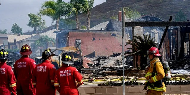 Fire crews work the scene of a small plane crash, Monday, Oct. 11, 2021, in Santee, California. At least two people were killed and two others were injured when the plane crashed into a suburban Southern California neighborhood, setting two homes ablaze, authorities said. (AP Photo/Gregory Bull)