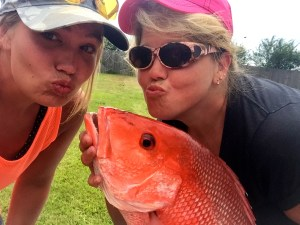 Lady anglers sharing the love with a red snapper caught deep sea fishing on Miss E along the AL Gulf Coast