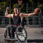 Strong basketball player in a wheelchair pose with a ball on open gaming ground.