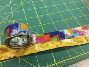 Image of thin tape being used to cover the edges of a duct tape strap.