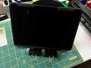 Image of iPad on a stand made of a bookend and two binder clips.