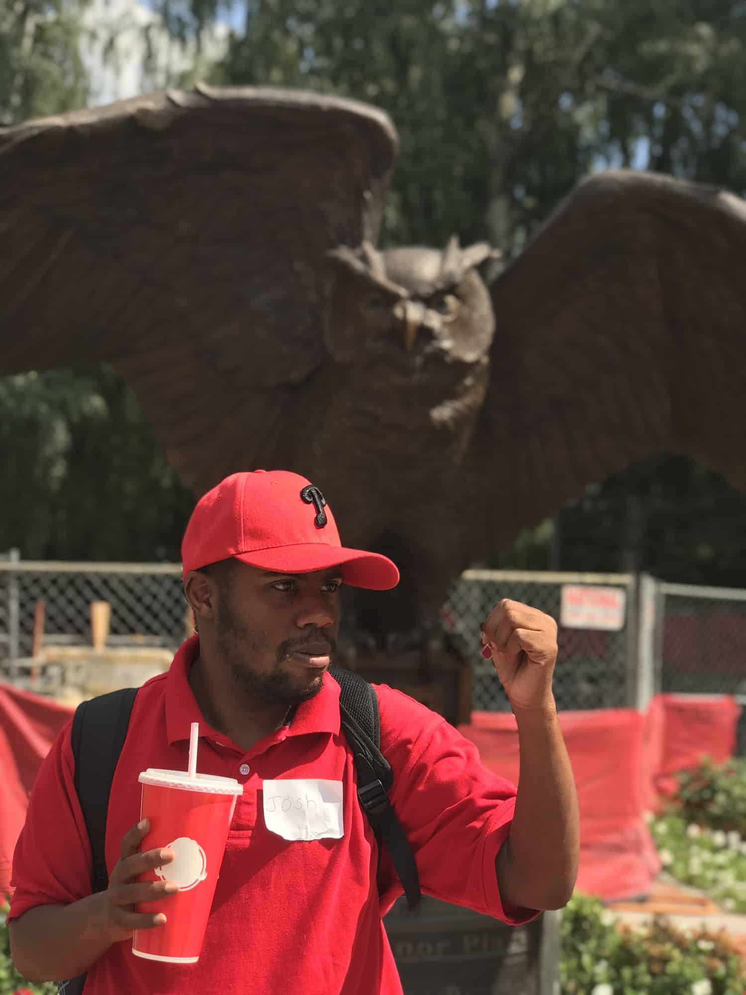 Image of a young man standing in front of the Temple Owl statue wearing red.