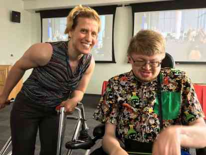 Image of woman with a wlaker and young AAC user in a wheelchair.