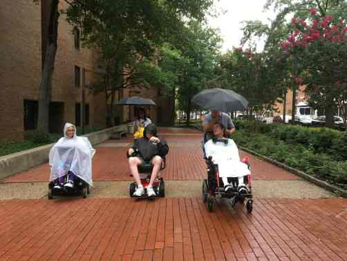 Image of wheelchair users with rain capes and umbrellas