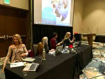 Image of women sitting at a table, presenting at Closing the Gap.