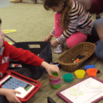 child using a AAC device in play