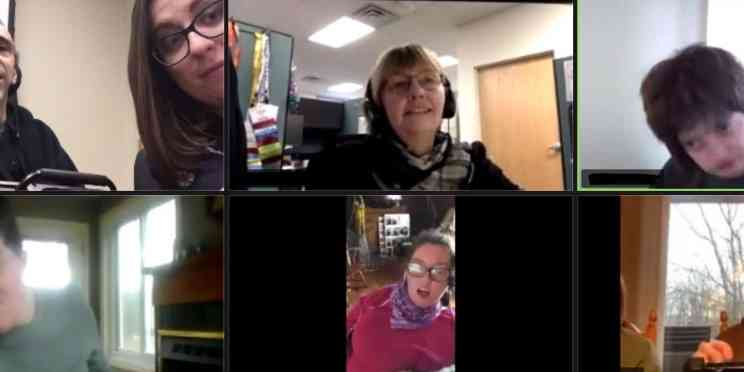 People participate in a Zoom video chat meeting. Seven individuals talk through telecommunication means. This image is a screenshot from the Zoom app.