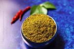 Karivepaku Podi | Andhra Curry Leaves Powder in a bowl on a blue background
