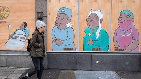 A woman passes a mural showing doctors and nurses in south London, as the UK continues in lockdown to help curb the spread of coronavirus
