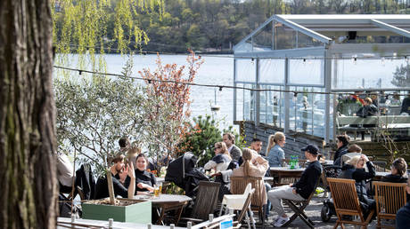 People enjoy the spring weather at an outdoor restaurant in Stockholm, Sweden April 26, 2020.
