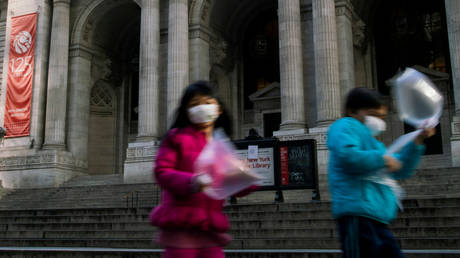FILE PHOTO: Children wearing face masks to protect from the coronavirus pass in front of the shuttered New York Public Library.