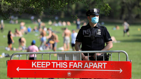 NYPD officer stands at the entrance of the Sheep Meadow in Central Park in Manhattan